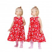 children and twins concept - two identical twin girls in red dresses looking somewhere