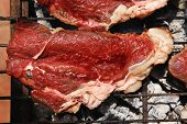 picture of brazier  - fresh raw beef meat fillet mignon on black grill grid over charcoal on brazier - JPG