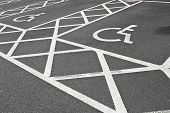 stock photo of handicap  - Designated Disabled car parking spaces reserved with white painted lines often set aside to give handicapped people accessibility in a car park - JPG