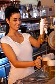 picture of bartender  - Portrait of attractive female bartender tapping beer in bar - JPG
