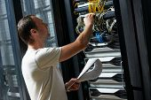 stock photo of racks  - network engineer working in server room - JPG