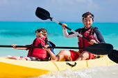 stock photo of canoe boat man  - Father and son kayaking at tropical ocean - JPG
