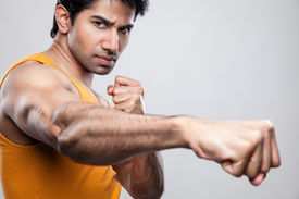 image of knockout  - Handsome Indian man giving a knockout punch