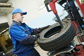 picture of auto garage  - Auto repairman loading automobile car wheel at tyre fitting machine during tire replacing - JPG
