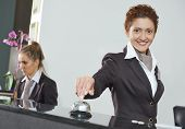 picture of front-entry  - Happy female receptionist worker standing at hotel counter with bell - JPG