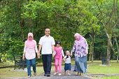 stock photo of southeast  - Asian family holding hands walking together on garden path - JPG