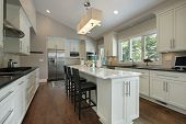 stock photo of light fixture  - Kitchen in luxury home with granite counter island - JPG