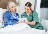 stock photo of nursing  - Female caretaker and senior woman using tablet PC in bedroom at nursing home - JPG