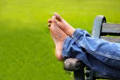 foto of spring break  - legs of relaxing adult person on a park bench wearing blue jeans on a beautiful sunny spring or summer day with blurred green grass in the background - JPG