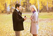 image of propose  - Love couple relationship and engagement concept - man proposing to a woman in the autumn park