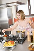 Attractive Woman Cooking Spaghetti And Tomato Sauce poster