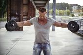 stock photo of hunk  - Attractive Muscular Hunk Man Lifting Weights Outdoor Looking Down for the Effort - JPG