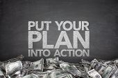 image of empower  - Put your plan into action on blackboard with pile of dollars - JPG