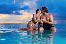 image of hand kiss  - Romantic couple sitting next to swimming pool - JPG
