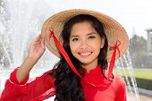 picture of conic  - Vietnamese woman in a red Ao Dai and conical hat standing in front of a fountain smiling at the camera - JPG