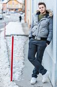 stock photo of stroll  - a handsome young man with winter clothes strolling in a small mountain town in europe - JPG