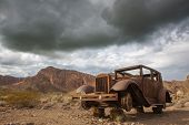 picture of wild west  - panoramic view of old antique rusty automobile in wild west environment - JPG