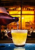 picture of alcoholic beverage  - lager beer drain from bottle to glass on table with beautiful lighting of snack bar use for alcohol drinking beverage in adult pub bar and restaurant - JPG