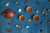 stock photo of teapot  - teapot and three cups with shuck on blue wooden table. Focus on the teapot top view. ** Note: Shallow depth of field - JPG