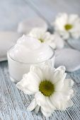 stock photo of cosmetic products  - Cosmetic cream with flowers and spa stones on wooden background - JPG