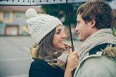 stock photo of rainy day  - Closeup of young beautiful couple embracing and laughing under the umbrella in an autumn rainy day - JPG