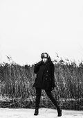 foto of cold-weather  - Fashion woman wearing a winter coat and fur cap and she posing front of the reeds cold rainy weather full length black and white image - JPG