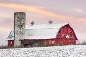 picture of red barn  - A snowy red barn with silo and basketball hoop is seen with a sunset sky of soft colors - JPG