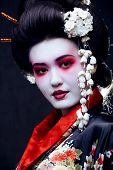 picture of geisha  - young pretty geisha in kimono with sakura and decoration on black background - JPG