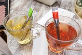 stock photo of tea bag  - red an green hot tea with tea bags on wood table - JPG