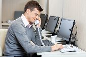 picture of telemarketing  - Young male call center employee using landline phone in office - JPG