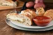 picture of cheese platter  - Homemade stromboli or stuffed bread with broccoli potatoes garlic onions and mozzarella cheese along with a side of marinara dipping sauce - JPG