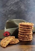 stock photo of biscuits  - Australian Anzac biscuits with soldier slouch hat on dark vintage background - JPG