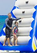 stock photo of inflatable slide  - Family Playing on an Inflatable toy at the beach - JPG