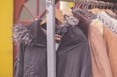 image of thrift store  - A bunch of winter jackets hanging on a rail outside - JPG