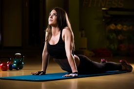 picture of yoga mat  - Attractive female athlete stretching on yoga mat in gym - JPG