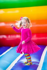 pic of inflatable slide  - Cute funny preschool little girl in a colorful dress playing jumping and bouncing in an inflatable castle having fun at a children birthday party on a kids playground in summer - JPG