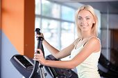 stock photo of elliptical  - Portrait of a beautiful young blond girl wearing a white top looking at the camera - JPG