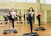 foto of step aerobics  - Group of young sportive women making step aerobics in the fitness class - JPG