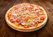 stock photo of leek  - Delicious pizza with fresh onions leek bacon and cherry tomatoes  - JPG