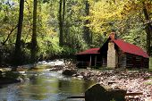 pic of log cabin  - old red roofed cabin on creek or river - JPG