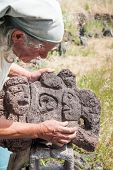 stock photo of stone sculpture  - Lava stone artist refining a sculpture using a softer red stone - JPG