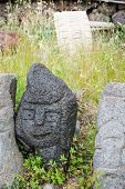image of stone sculpture  - Lava stone sculpture of a stylised man poured with water to make its design stand out - JPG