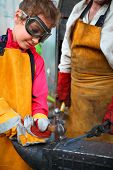 picture of goggles  - Girl in goggles and yellow apron with  hammer hitting anvil in smithy - JPG