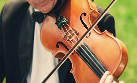 picture of bowing  - Musician with bow tie plays violin with fiddle bow at the outdoor concert - JPG