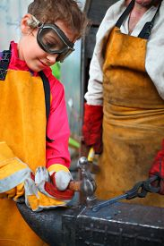image of anvil  - Girl in goggles and yellow apron with  hammer hitting anvil in smithy - JPG