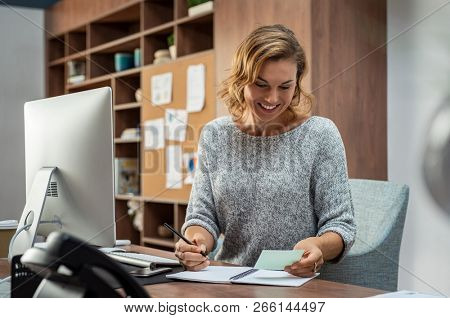 poster of Smiling busy employee in casual reading notes and writing on notebook. Happy mature business woman r