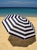 Striped umbrella against sandy beach and ocean