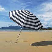 stock photo of langkawi  - Striped umbrella on a sandy beach of Langkawi island - JPG