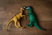 Top View Closeup Of A Yellow And Green Big Toy Dinosaurs Facing Each Other On Dark Brown Wooden Parq poster
