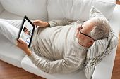 medicine, technology and healthcare concept - senior patient having video chat with doctor on tablet poster